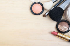 Top view of woman earth tone cosmetics. Woman earth tone cosmetics (make-up) - eyeshadow, brush on, lipstick, powder, brush. Top view with space for text royalty free stock photos