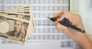 Top view woman hand hold pen and on Statement or financial report and japan money in business concept.. Royalty Free Stock Images