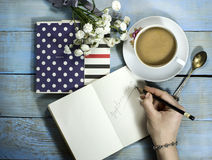 Top view of woman hand writing in notebook. On wooden table with white flower and cup of coffee royalty free stock photo