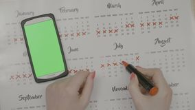 Top view of woman hands crossing on calendar days planning birth prevention with green screen smartphone tracking period -. Top view of woman hands crossing on stock footage