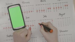 Top view of woman hands crossing calendar days planning to save money while swiping green screen smartphone to check dates -. Top view of woman hands crossing stock footage