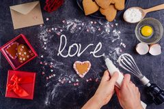 Top view woman hands making meringue cream lettering Love on the black stone background with ingredients, gift box and decor detai. Ls. Valentine`s day concept Stock Photo
