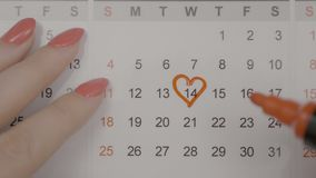 Top view of woman hands marking with a heart valentines day on calendar with red pen to celebrate it with her boyfriend -. Top view of woman hands marking with a stock footage