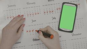 Woman hands marking period dates on calendar planning birth control while looking at smartphone with green screen on her desk -. Top view of woman hands marking stock video footage
