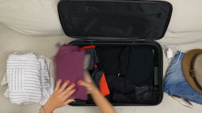 Top view of woman hands with red nails filling suitcase with folded clothes for a travel trip. Top view of woman hands with red nails filling suitcase with stock video footage