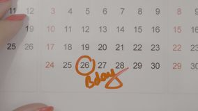 Top view of woman hands signing birth day on calendar and counting the days to it -. Top view of woman hands signing birth day on calendar and counting the days stock video footage