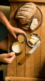 Top view woman has breakfast adds milk to coffee. Top view of woman adding milk to coffee at the table with rye bread and butter sandwich royalty free stock images