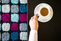 Top View Woman Holding Coffee Mug. On a Table with a colorful carpet background Royalty Free Stock Images