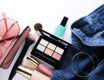 Top view of woman jeans shirt, concealer pallet, lip gloss, nail polish, bracelet, powder brush on white background. Beauty and fashion concept Royalty Free Stock Photos