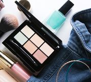 Top view of woman jeans shirt, concealer pallet, lip gloss, nail. Polish, bracelet, powder brush on white background. beauty and fashion concept Stock Photos