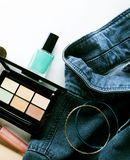 Top view of woman jeans shirt, concealer pallet, lip gloss, nail. Polish, bracelet, powder brush on white background. beauty and fashion concept Stock Images