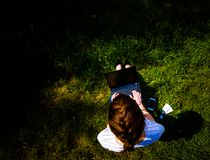 Top view of woman with laptop notebook and smartphone sitting on the green grass. She is in blue jeans and a white t-shirt stock images