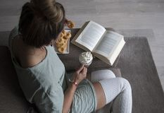 Top view of woman reading book at home on couch with hot chocolate milk and cookies royalty free stock photos