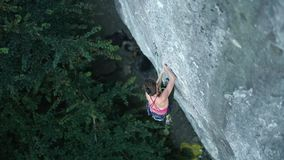 Top view woman rock climber climbing on tough sport route, looking, searching, reaching and gripping holds
