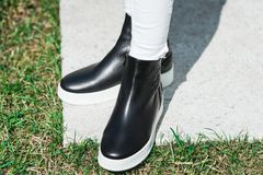 Top View Of Woman`s Black Leather Ankle Boots. Outdoor Shot Over White Stone in park royalty free stock photography