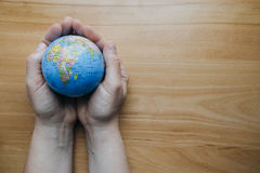 Top view of woman`s hand with globe on wooden table. Empty space Royalty Free Stock Images