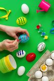 Woman`s hand paints eggs. Top view woman`s hand paints eggs, on green background stencils, paints. ribbons, watering can. preparation for the holiday royalty free stock photos