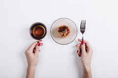 Top view of a woman's hands holding a cup of tea and fork, on th Stock Photography
