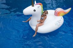 Woman with big inflatable unicorn in the pool. Top view of woman`s hands and legs laying down on the big white inflatable unicorn in the pool Royalty Free Stock Photos