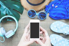 Top view of woman`s hands using smartphone with summer items on. Background, Focus on mobile phone, Summer lifestyle, Mobile application stock photography