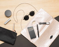 Top view of woman`s small bag, cosmetic, sun glasses and smart p Royalty Free Stock Images