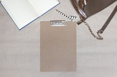 Top view of woman`s workplace,empty clipboard,notebook,pen,bag.Concept of working table at the office royalty free stock photography