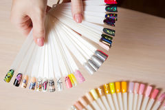 Top view woman selects yellow color shellac nail polish.Nail technician shows the color palette of nail services in beauty salon. Manicure and pedicure nail Stock Photos