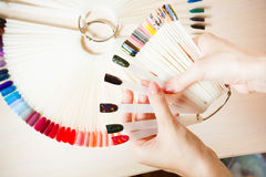 Top view woman selects yellow color shellac nail polish.Nail technician shows the color palette of nail services in Royalty Free Stock Photo