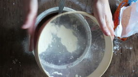 Top view of woman sieving flour in plate stock footage