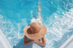 Top view of woman in straw hat relaxing in swimming pool at luxu Stock Images