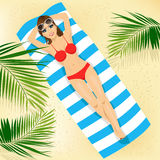 Top view of woman with sunglasses in bikini lying on colorful beach towel Royalty Free Stock Image