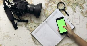 Top view woman traveler hands planning holiday using mobile phone app vintage map from above. Top view. woman traveler hands using smart phone with green screen stock video footage