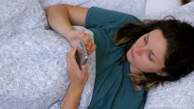 Top view of a Woman using a smartphone lying on a white bed in the morning stock video