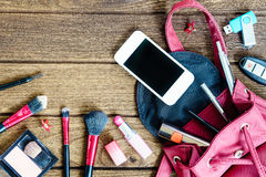 Top view of women bag stuff female cosmetic accessories on woode Royalty Free Stock Image