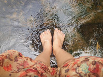 Top view of women leg and feet dip in crystalline stream Royalty Free Stock Photography