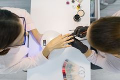 Top view, woman manicurist doing manicure, painting nails, using ultraviolet lamp for fixing gel nail polish. Nail and hand care. Top view, women manicurist royalty free stock photography
