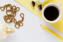 Top view of women`s business work desk. Fresh flat lay fashion feminine workspace with cup of coffee, cosmetics and jewelry. On white background royalty free stock image