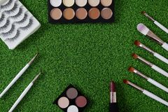 Top view of women`s cosmetic on green background royalty free stock photo