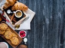 Top view of a wood table full of cakes, fruits, coffee, biscuits Royalty Free Stock Photo