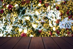 Top view wood table on soft blur abtract bokeh and Christmas tre. E background, can be used to present products Royalty Free Stock Photos