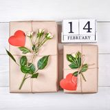 Top view of wooden block calendar and gift boxes with flowers royalty free stock image