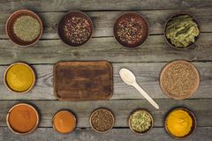 Board and spoon among bowls with spices royalty free stock photo