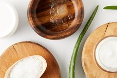 top view of wooden bowl with aloe vera juice, organic cream in container and spoon with salt on wooden slices, aloe vera leaves on stock photos
