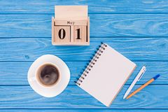 Top view of wooden calendar with date of 1st may, coffee cup, blank textbook and pens, international workers day concept Stock Photography