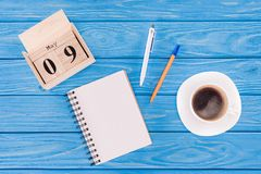 Top view of wooden calendar with date of 9th may, coffee cup, empty textbook and pens, victory. Day concept royalty free stock image