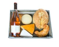 Top view of a wooden crate with vine, cheese and pastry on white background stock photo