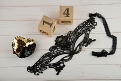 Top view on wooden cubes with numbers 1, 4 golden heart and black lace mask royalty free stock photos