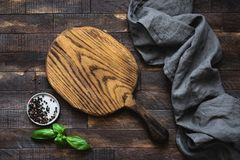 Top view of wooden cutting board, spices and kitchen textile, food background Stock Image