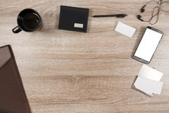 Wooden desk with smartphone, headphones, pen, name tag, wallet,. Top view on wooden desk with smartphone with empty copy space, black headphone earpieces and Royalty Free Stock Images