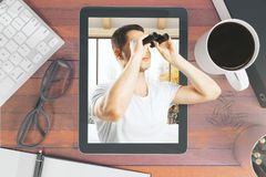 Research concept. Top view of wooden desktop with abstract businessman using binoculars on tablet screen, coffee cup, keyboard and other items. Research concept Stock Photos